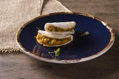 Tapioca deliziosa, uno spuntino brasiliano fatto con la farina della manioca e gamberetto, manioca su un piatto blu immagini stock libere da diritti