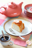 Tapioca Pudding. Piece of Brazilian Tapioca Pudding with Caramel Topping on white plate, cup of coffee and light orange teapot, on colorful napkin Royalty Free Stock Photos