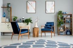 Tapis bleu dans l'intérieur gris de salon avec les affiches et la table en bois entre les fauteuils photographie stock libre de droits