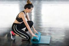 tapis bleu de yoga de jeune roulement asiatique de femme de forme physique apr?s s?ance d'entra?nement dans le gymnase images libres de droits