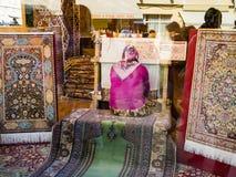 Tapis d'armure de femme dans la fenêtre de la boutique à Istanbul Photo stock