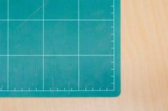 Tapis de coupe sur la table en bois, stationnaire Images stock