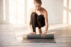 Tapis de déroulement femelle de yoga avant exercice de séance d'entraînement image libre de droits