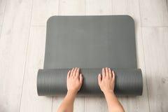 Tapis de roulement de yoga de femme sur le plancher à l'intérieur photo libre de droits