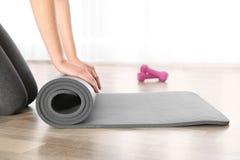 Tapis de roulement de yoga de femme sur le plancher à l'intérieur photographie stock