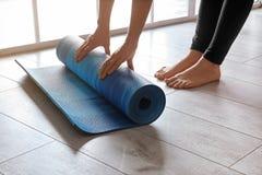 Tapis de roulement de yoga de femme sur le plancher ? l'int?rieur images stock