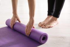 Tapis de roulement de yoga de femme sur le plancher ? l'int?rieur images libres de droits