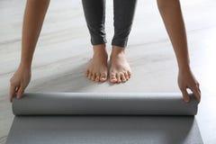 Tapis de roulement de yoga de femme sur le plancher ? l'int?rieur photo libre de droits