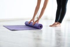 Tapis de roulement de yoga de femme sur le plancher ? l'int?rieur image libre de droits