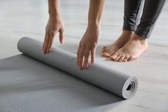 Tapis de roulement de yoga de femme sur le plancher ? l'int?rieur photographie stock libre de droits