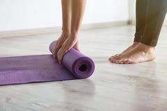 Tapis de roulement de yoga de femme sur le plancher ? l'int?rieur photos libres de droits