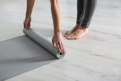 Tapis de roulement de yoga de femme sur le plancher ? l'int?rieur photographie stock