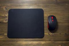 Tapis de souris et souris d'ordinateur sur une publicité en bois de fond images stock