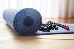 Tapis de yoga avec des perles de mala Photographie stock