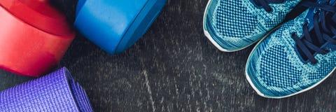 Tapis de yoga de BANNIÈRE, chaussures de sport, haltères et bouteille de l'eau sur le fond bleu Mode de vie, sport et régime sain Images libres de droits