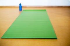 Tapis de yoga, bouteille d'eau sur le fond jaune Équipement pour le yoga Images stock