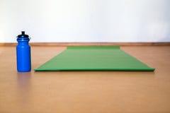 Tapis de yoga, bouteille d'eau sur le fond jaune Équipement pour le yoga Mode de vie sain de concept couleur Images stock