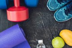 Tapis de yoga, chaussures de sport, haltères et bouteille de l'eau sur le CCB bleu Photos stock