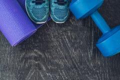 Tapis de yoga, chaussures de sport, haltères et bouteille de l'eau sur le fond bleu Mode de vie, sport et régime sains de concept Photos stock
