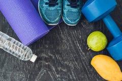 Tapis de yoga, chaussures de sport, haltères et bouteille de l'eau sur le CCB bleu Image libre de droits