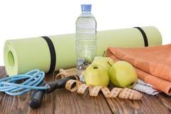 Tapis de yoga et plan rapproché de bouteille d'eau Article de sport, trois pommes vertes et une corde de saut Photo libre de droits