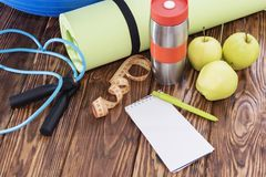 Tapis de yoga et plan rapproché de bouteille d'eau Article de sport, trois pommes vertes et une corde de saut Images libres de droits