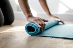 Tapis de yoga de roulement de femme après avoir fini avec l'exercice images libres de droits