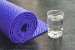 Tapis, eau, orange et mangue de yoga sur un fond en bois Équipement pour le yoga Mode de vie, régime et sport sains de concept Co Photographie stock libre de droits