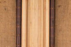 Tapis en bambou foncé et léger sous forme de mensonge de rouleau sur renvoyer Photographie stock libre de droits