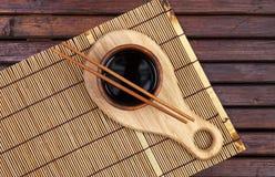 Tapis en bambou, sauce de soja, baguettes sur la table en bois foncée Vue supérieure avec l'espace de copie photos libres de droits