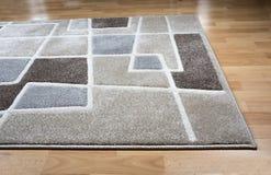 Tapis moderne sur le plancher de parquet en stratifié image stock