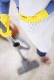 Tapis propre de femme au foyer avec l'aspirateur Images stock