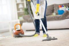 Tapis propre de femme au foyer avec l'aspirateur Image stock
