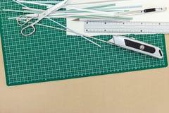 Tapis vert de coupe avec la règle de ciseaux, de coupeur et en métal sur le bureau Images libres de droits