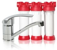 Tapkraan en drievoudige water schoonmakende filter op wit stock foto's