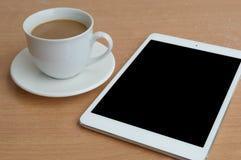 Taplet avec la tasse noire d'écran et de café sur le bureau en bois Images libres de droits