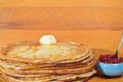 Tapotement de beurre de fonte sur une pile des crêpes Photo stock