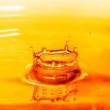 Tappa att falla in i orange vatten med färgstänk Fotografering för Bildbyråer