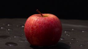 Tappa sötvatten på ett rött äpple på svart bakgrund stock video