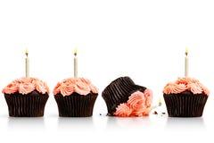 Tappad muffin i rad av muffin med stearinljus på whit Royaltyfri Foto