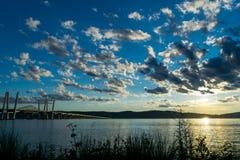 Tappan Zee bro som leder över Hudson River in mot nytt - ärmlös tröja, medan en härlig solnedgång tänder upp moln-fylld royaltyfria foton