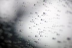 tappar glass vatten Utvald fokusdroppe av vatten på exponeringsglaset utanför bilen i den regna dagen Arkivfoto