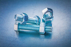 Tapped nuts and screw bolts on metallic background Royalty Free Stock Image