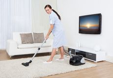 Tappeto di pulizia della domestica con l'aspirapolvere Immagini Stock