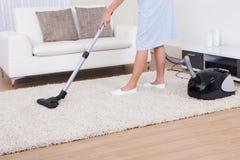 Tappeto di pulizia della domestica con l'aspirapolvere fotografia stock libera da diritti