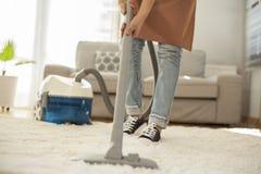 Tappeto di pulizia della donna con un aspirapolvere nella sala Fotografie Stock