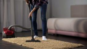 Tappeto hoovering femminile della stanza durante la pulizia generale, funzionamento della casa, ordine immagini stock