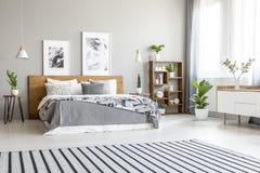Tappeto a strisce nell'interno luminoso spazioso della camera da letto con i manifesti fotografia stock libera da diritti