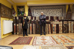 Tappezzi il venditore che offre i tappeti orientali variopinti al suo deposito fotografia stock libera da diritti