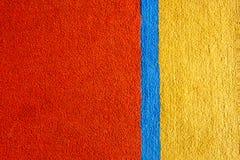 Tappezzi le caratteristiche di struttura ha creato il fondo giallo rosso del tappeto Fotografia Stock Libera da Diritti